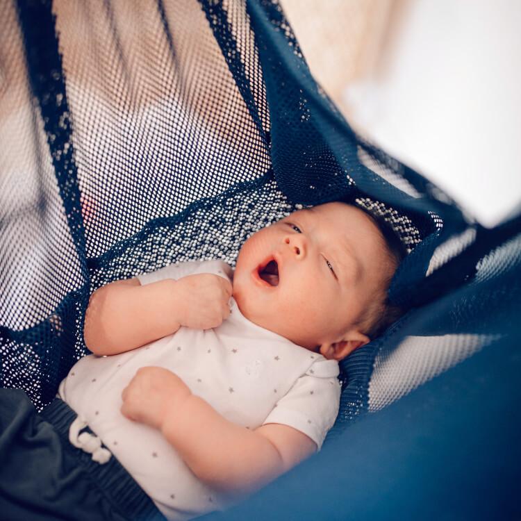Baby müde in blauer Federwiege MATTI liegend