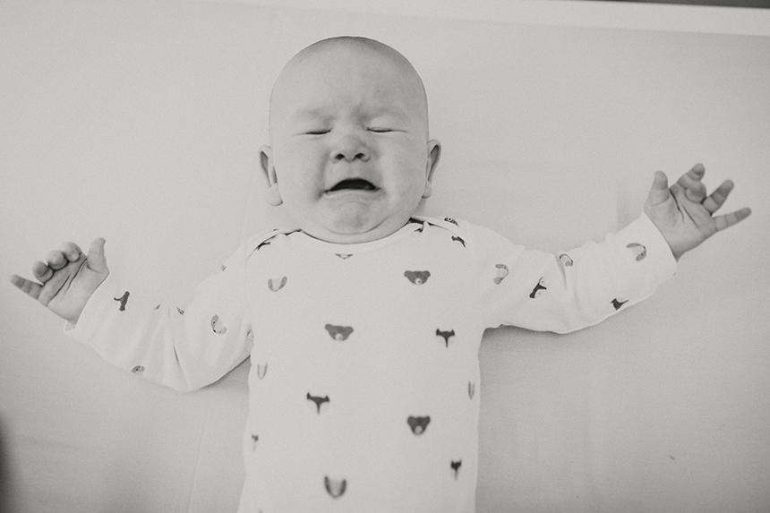 Weinendes Baby mit ausgestreckten Armen in schwarz-weiß